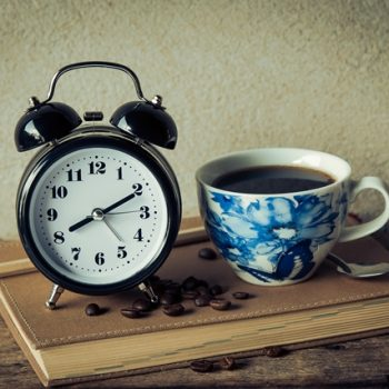 Alarm clock next to a vintage china cup